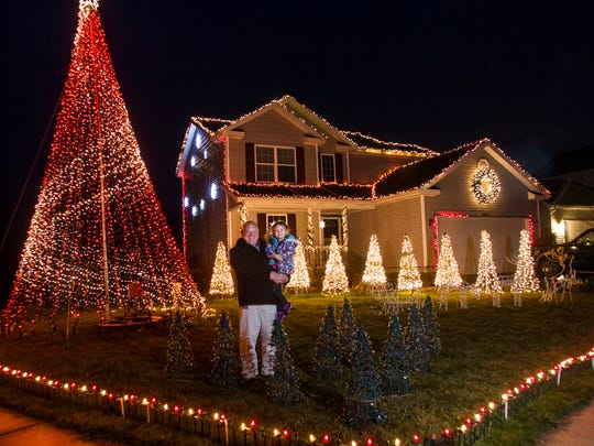 "Jeremy Brown and his daughter Mckelvy, 4, in front of their ""Brown Family Christmas Lights Show"" home in Delhi Township."