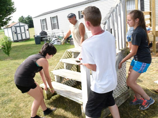 Members of the Chambersburg Project replace a porch and steps at a mobil home Tuesday, July 12, 2016 in Shippensburg.