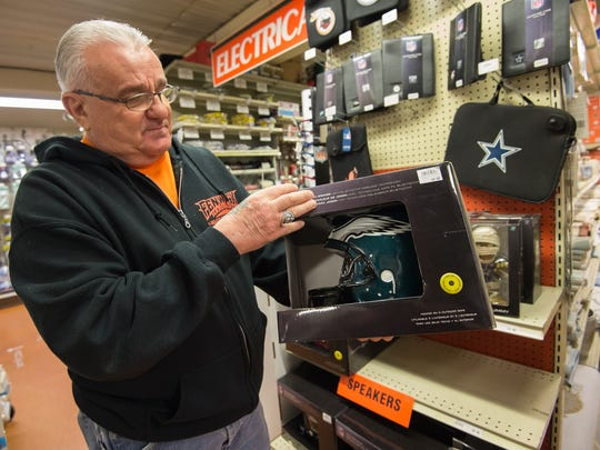 Ron Lapalomento, a salesman at Fenwick Island Hardware, holds up a Philadelphia Eagles speaker for sale in their NFL Pro Shop section of the hardware store.