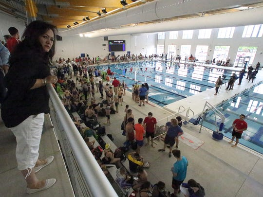 Arcy Puga, left, looks out for her granddaughter from the elevated grand stands overlooking the new Olympic-size pool inside the new West Side natatorium following its grand opening Saturday. A meet of various local swim teams immediately began using the facility.
