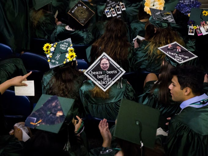 Students point at each others decorated graduation
