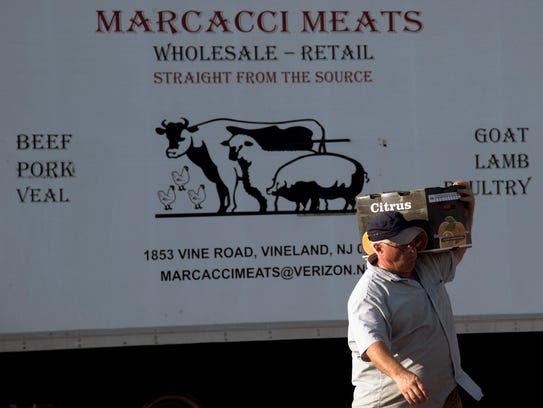 A man carries a box of oranges from a Marcacci Meats