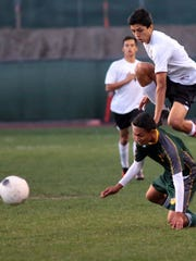 Edgar Duran of Palm Springs (7, white) leaps over Coachella Valley's Pedro Barrosos (3, green) while trying to get to the ball as the Indians host Coachella Valley Wednesday night in a Desert Valley League game. The teams are battling one another to gain better positioning as playoffs near.