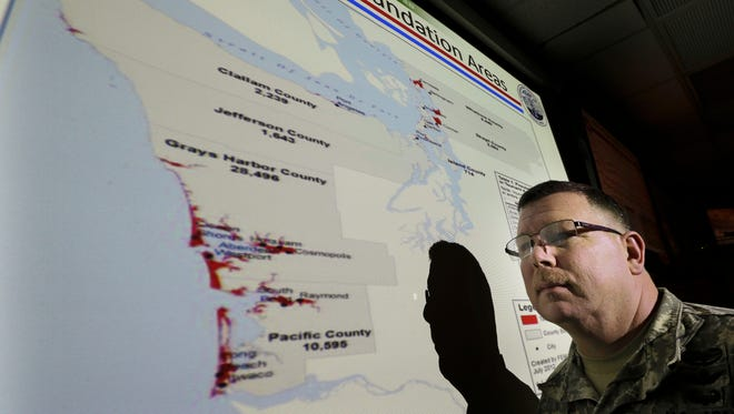 In this Jan. 20, 2016 file photo, Lt. Col. Clayton Braun, of the Washington State Army National Guard, poses for a photo at Camp Murray in Washington state in front of a slide showing areas in Washington state that could be affected by tsunamis.
