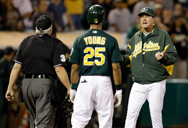 Athletics manager Bob Melvin, right, asks home plate umpire Dana DeMuth to review the path of a ball hit by A's Chris Young which would have won the game in the ninth inning against the Astros.