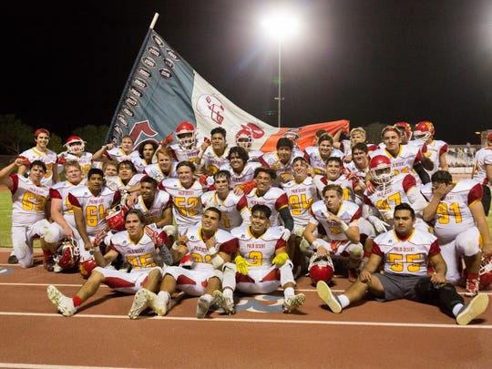 The Palm Desert High School football team celebrates with the Victory Flag after beating rival La Quinta 24-17 in triple overtime on Friday night.