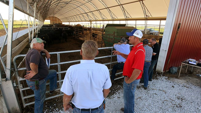 Livestock farmer Jacob Schmidt (right) talks with attendees at an  open house in front of a new hoop barn used for calving and finishing cattle at Schmidt's farm in rural Camp Point, IL The barn is designed to improve cattle comfort and performance, which in turn is expected to boost the operation's efficiency.