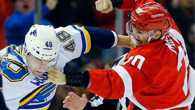Red Wings left wing Drew Miller (20) fights Blues defenseman Petteri Lindbohm (48) in the third period.