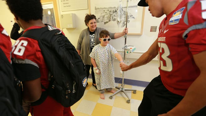 Trent Larson fist bumps Washington State's Nnamdi Oguayo on Thursday during a visit by members of the team to El Paso Children's Hospital. Trent wore the sunglasses given to him by the team as he walked around the floor with his mother, Joy Larson.