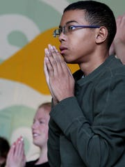 Sophomore Malik Orr finishes a yoga posture during Mindful Studies class at Wilson High School in Portland, Ore. The year-long course is one of a growing number of programs that are incorporating mindfulness, yoga and meditation into school curriculums to bring socio-emotional benefits to students.