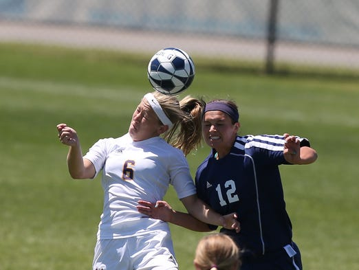 Nevada's Kaylee Kruschwitz, left, heads the ball as Regina's Katie Wick collides into her during the Iowa girls high school 1A soccer tournament at Cownie Sports Complex in Des Moines on Friday, June 13, 2014.