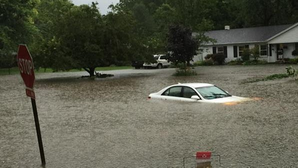 A car is nearly submerged in floodwaters on East 77th Street in Arrowhead Estates on Sunday, July 26, 2015. The driver escaped.