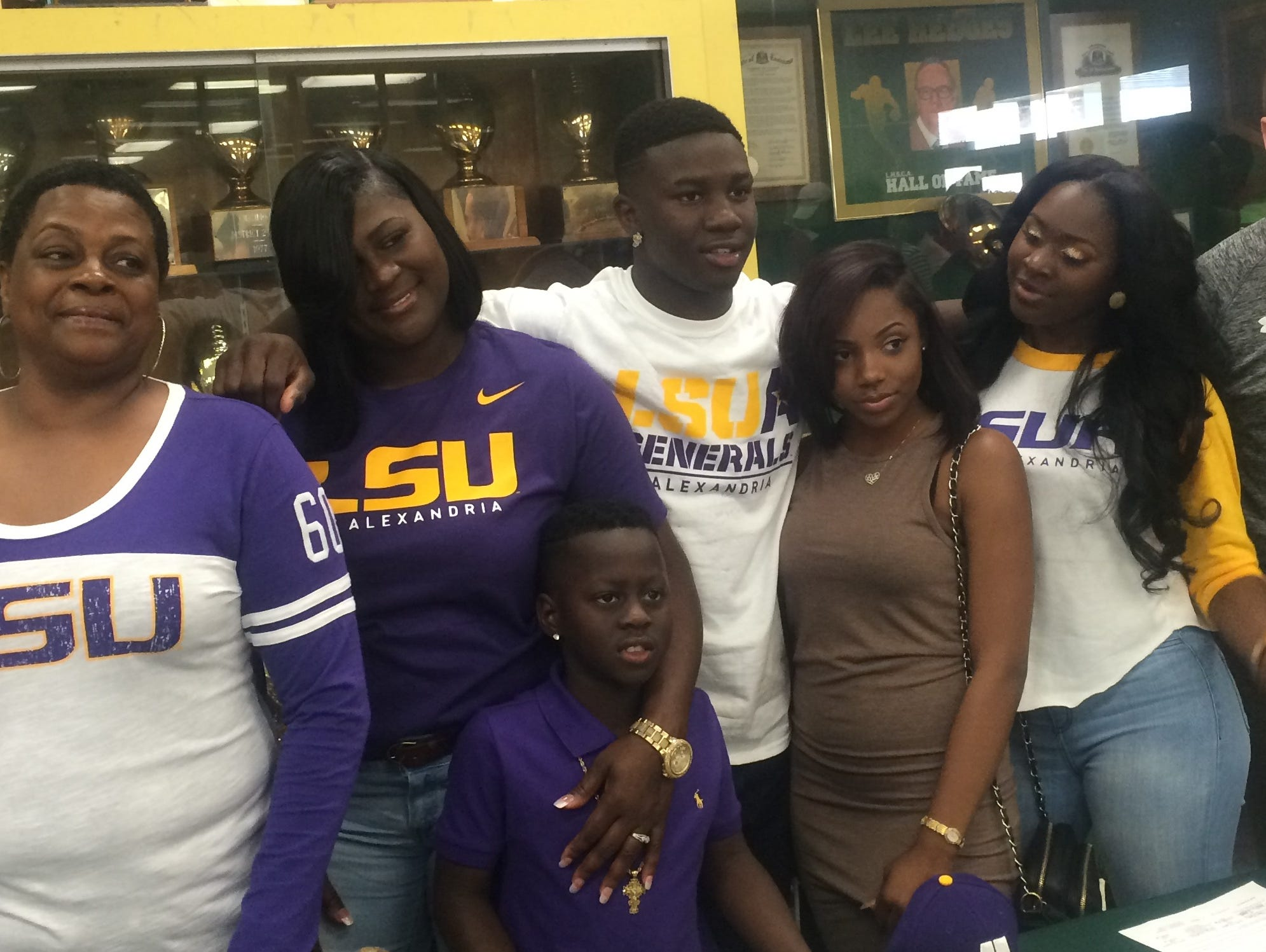 Toronco Loston, center, with his family and LSUA assistant coach Casey Apetrei.