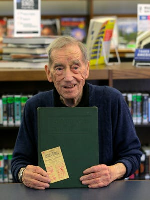 Frank Ryan of Bound Brook holds the stamped check out card and the book he checked out 71 years ago before officially returning the book at the Bound Brook Memorial Library in Bound Brook, NJ Monday February 22, 2016.