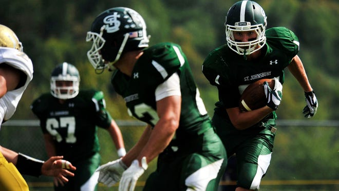 St. Johnsbury's Mathew Roy, right, carries the ball during a high school football game against Essex last season. Roy and the Hilltoppers defeated Hartford in Week 1 last week to earn the No. 1 ranking in the Varsity Insider power rankings.