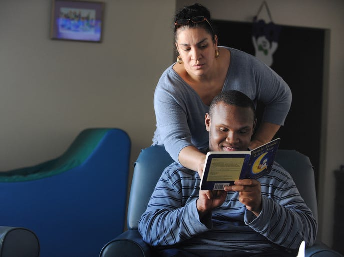 Assistant Supervisor Maria Rosado, who has been with the facility for 19 years, helps DuVerney, 21, read before dinner at the Lahser Respite Home in Beverly Hills, Mich., on Sept. 22, 2014.  The home, which provides short-term relief services for autistic and developmentally disabled clients, is scheduled to close on Nov. 1  because of state budget cuts.
