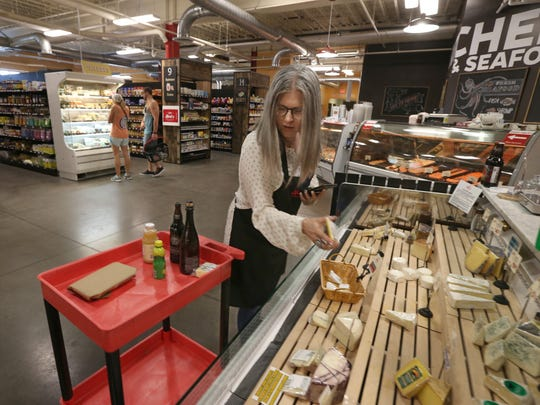 Amy Jerman stops in the cheese section as she fills an online grocery delivery order.