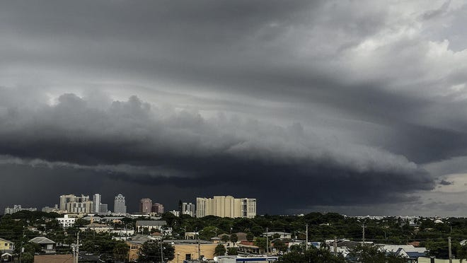 A storm moves over downtown West Palm Beach producing heavy rain and lightning, August 13, 2015.