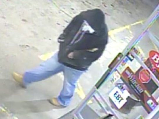 An armed man leaves BJ's Gas and Food Store in Candler