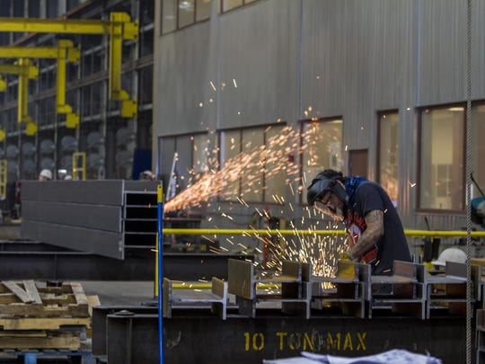 ADF International employees grind the edges of steel beams at the company's steel fabrication facility in Great Falls.