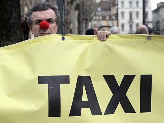 An Italian Taxi driver wears the red nose of clown