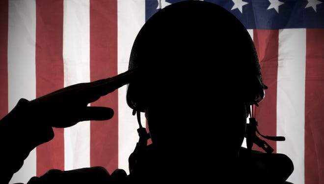 Soldier salutes the American flag.