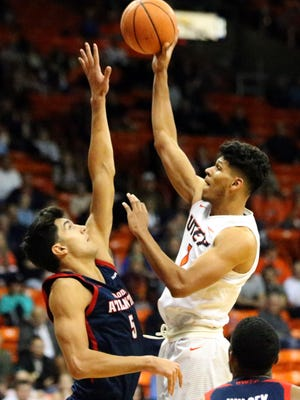 UTEP junior forward Paul Thomas, 1, rises up for a basket despite the efforts of William Pfister, 5, of Florida Atlantic Thursday night in the Don Haskins Center.
