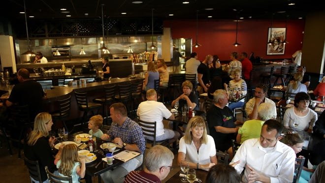 Customers fill the new bar and dining area at Houdini's Escape Gastropub in Appleton.
