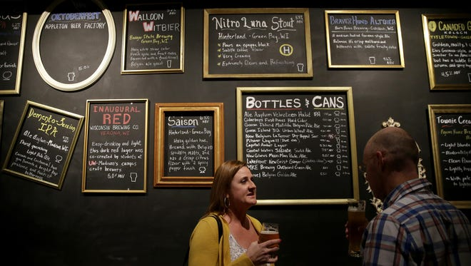 Stacey Ruiz talks with Sean Brownson in front of a wall listing some of the beers offered at Lion's Tail Brewing Co. during a Future Neenah networking event. The brewery officially opens Friday.