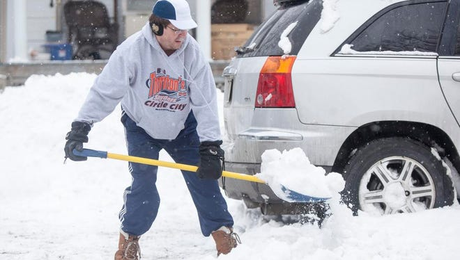 Ken Byrd shovels out his car Sunday afternoon along North Elm Street. Area drivers had to deal with slick conditions on roads and buried vehicles following snow Saturday and Sunday.