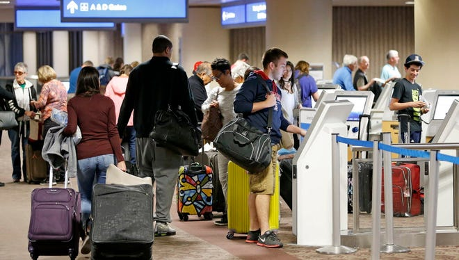 Thanksgiving holiday travelers check in at Phoenix Sky Harbor International Airport on Nov. 23, 2016, in Phoenix.