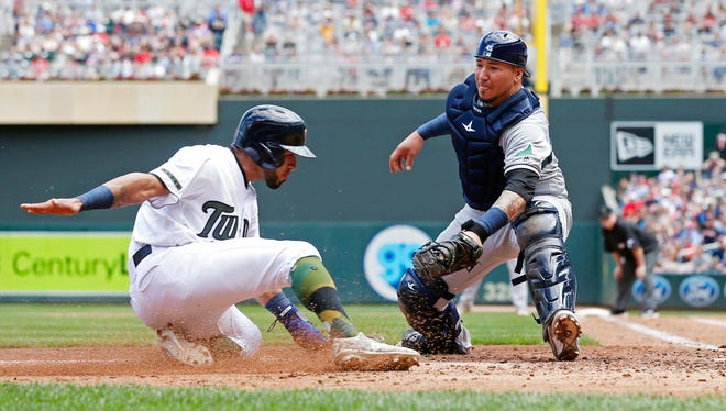 Minnesota Twins' Eddie Rosario,right, tries to score past Tampa Bay Rays catcher Jesus Sucre in the fourth inning of a baseball game Sunday, May 28, 2017 in Minneapolis.