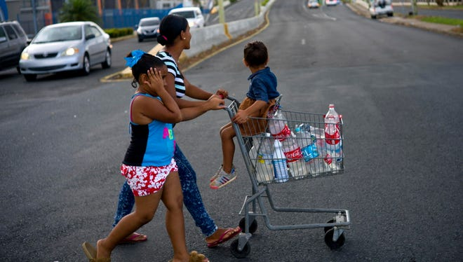 A resident collects water in Bayamon, Puerto Rico, on Sept. 28, 2017.