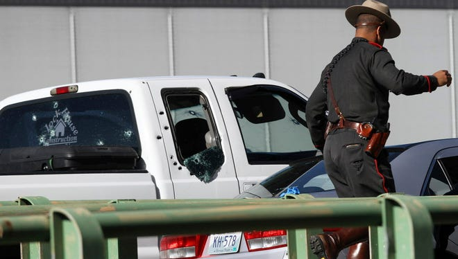 A Rhode Island state police trooper walks past a white pickup truck with multiple bullet holes in the windows and right side at the scene of a shooting on Interstate 95 in Providence,  R.I., on Nov. 9, 2017.