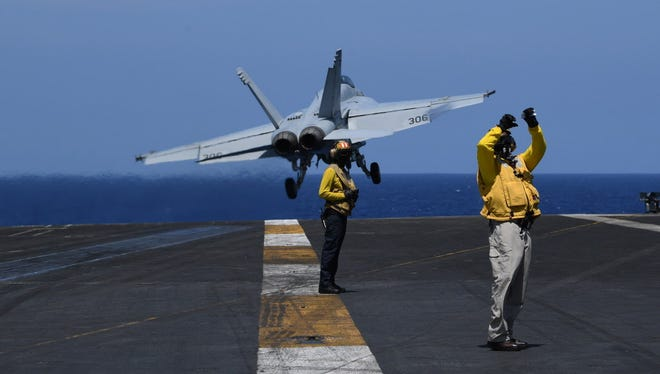 U.S. sailors stand on the flight deck while an FA-18 hornet fighter jet takes off, during a routine training aboard U.S. aircraft carrier Theodore Roosevelt in the South China sea on April 10, 2018.  The carrier group Theodore Roosevelt is transiting through the South China sea on its way to the Philippines from Singapore after participating in Operations Inherent Resolve (OIR) and Operation Freedom's Sentinel (OFS) in Syria, Iraq and Afghanistan. / AFP PHOTO / TED ALJIBETED ALJIBE/AFP/Getty Images ORIG FILE ID: AFP_13W0U4