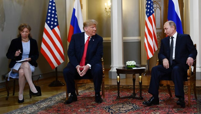 Russian President Vladimir Putin (R) and US President Donald Trump (2L) attend a meeting in Helsinki, on July 16, 2018. US Democratic lawmakers on July 19, 2018, pushed for Congress to subpoena Trump's interpreter, Marina Gross (L), amid a growing sense of alarm over the private summit in Helsinki between Trump and Putin. The two presidents held a two-hour closed-door negotiation with no other officials present save for the leaders' interpreters.
