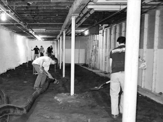 "The Old Labor Hall has been hit by three floods since reopening in 2000. The Barre Historical Society is taking steps to ""wet-proof"" the hall since it not possible to totally flood proof the basement. The Historical Society has been awarded a FEMA flood mitigation grant but needs matching funds.  Photo shows workers excavating dirt from basement floor prior to pouring from cement."