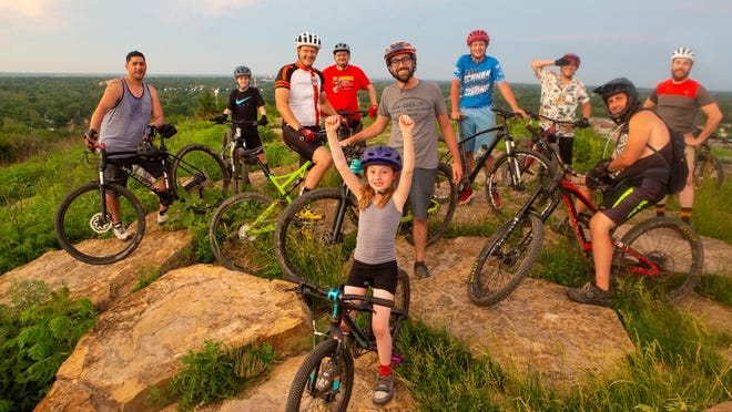 Meredith Clark and Kasey Clark, pictured middle, stand with their mountain bikes with, from left, Juan Gonzales, Brayden Stice, John Steflik, Howard Stice, Alex Steflik, Tyler Brown, Allen Reeb and Chris James on top of Azura Trails at Skyline Park on Monday evening. Kasey Clark has been at the forefront of change to this trail system surrounding Burnett's Mound, Topeka's highest point.