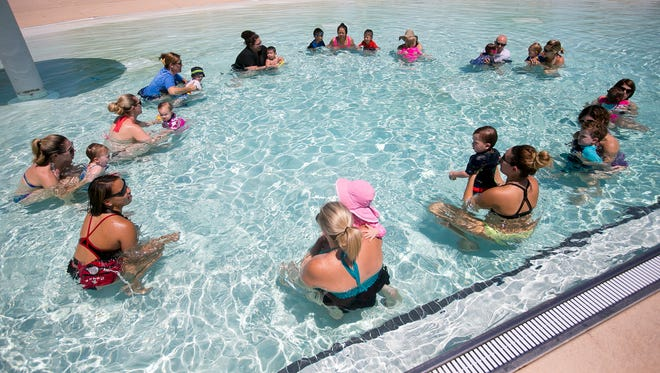 Parents swim with their kids during a class at the Paradise Valley City Swimming Pool on Monday, June 15, 2015.