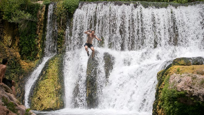 Jesse Barber jumps off the old dam at Fossil Springs on Friday, June 12, 2015.