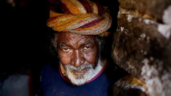 "In this April 25, 2016 photo, Saeed Ghailan Mohammed, 60, from a community who call themselves the ""Muhammasheen,"" or ""the Marginalized,"" who fled the city of Taiz due to the ongoing civil war, stands inside his hut in a slum area of Sanaa, Yemen."