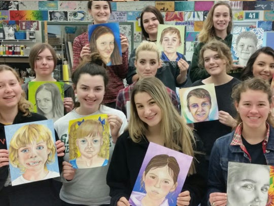 Seneca High school art majors show portraits they drew from photographs of orphans in Ukraine they have never met. The art was done for the Memory Project, a nonprofit that connects youth internationally through art and sends the portraits to the Ukrainian children.