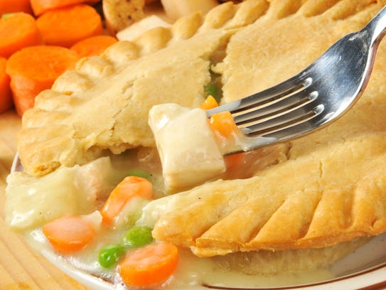 Closeup of a forkful of chicken pot pie with ingredients