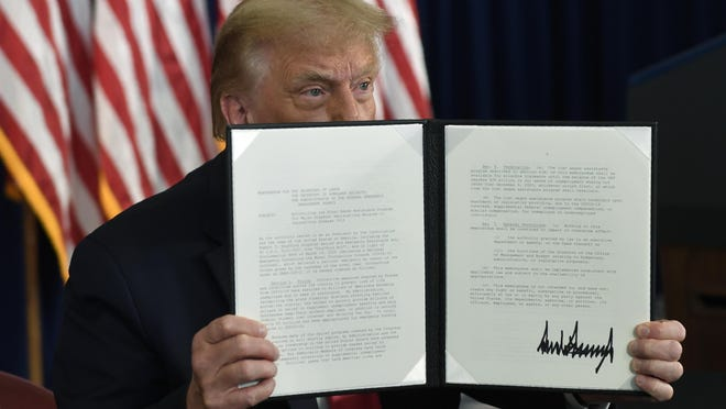President Donald Trump signs an executive order during a news conference Saturday at the Trump National Golf Club in Bedminster, N.J.