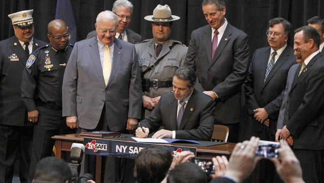 New York Gov. Andrew Cuomo signs the SAFE Act Jan. 16, 2013, at Rochester's City Hall.