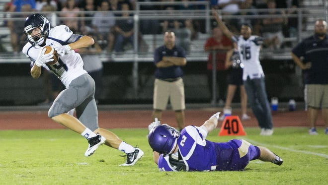 Higley junior receiver Bryce Gilbert (14) breaks a tackle and runs for a touchdown during the game between Queen Creek and Higley, Friday, September 25, 2015, in Queen Creek, Ariz.