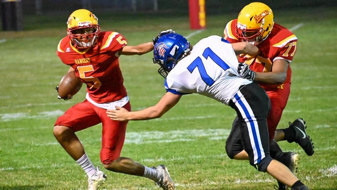 Reading's Gabe Rife (5) stiff arms a Springport defender during Friday's game. Sam Fry/Daily News