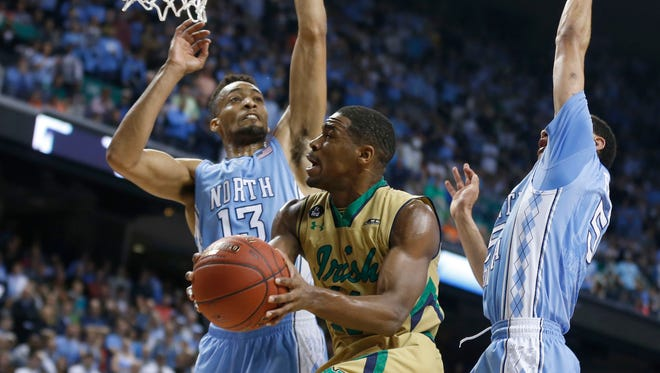 Notre Dame's Demetrius Jackson (11) gets around North Carolina's J.P. Tokoto (13) and Marcus Paige (5) in the first half on Saturday, March 14, 2015, during the championship game of the ACC Tournament at the Greensboro Coliseum in Greensboro, N.C. (Ethan Hyman/Raleigh News & Observer/TNS)