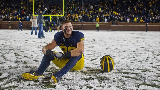 Michigan tight end Jake Butt sits on the snow-covered field after a game against Indiana in Ann Arbor on Saturday, Nov. 19, 2016.