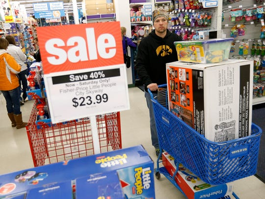 Travis Ledvina of Waukee pushes a cart full of toys Friday, Nov. 27, 2015, as he follows his wife through Toys R Us in Clive. The couple said they had been shopping for Black Friday deals since Thursday night.